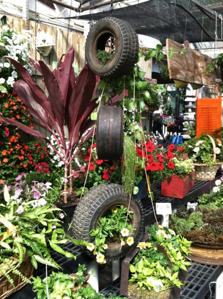 Tires used as hanging planters in a small garden